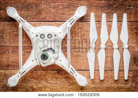 FORT COLLINS, CO, USA - JANUARY1, 2017:  DJI Phantom 4 pro quadcopter drone with propellers on a rustic wooden table, bottom view showing a camera and sensors.