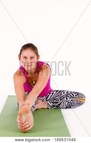 Supple flexible young woman doing exercises working out on a yoga mat, stretching forwards towards her bare foot in the foreground of the view