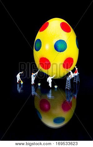 Miniature figurines painters painting yellow easter egg isolated on black background