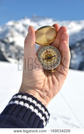Compass in the hand against Alpine scenery