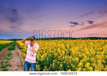 photographer in the field of yellow flowers.
