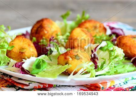 Fried potato balls with salad leaf mix and basil on a plate. Small golden fried balls made from mashed potatoes, eggs, flour, salt and pumpkin seeds. Vegetarian dish. Closeup