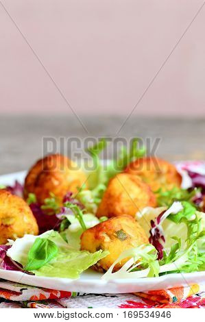 Fried mashed potato balls with salad leaf mix and basil on a plate. Small fried balls made from mashed potatoes, eggs, flour, salt and pumpkin seeds. Vertical photo