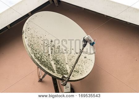 Weathered grungy dirty satellite dish in need of maintenance on brown wall