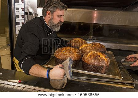 Baker taking out baked panettone from oven