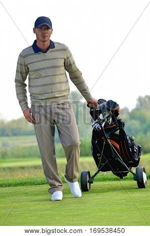 Portrait of young man carrying trolley with golf bag
