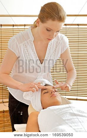 Young woman receiving head massage from masseuse