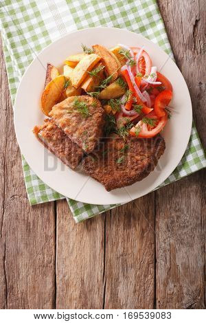 Veal Breaded Rump Steak And Garnished With Vegetables Close-up. Vertical Top View