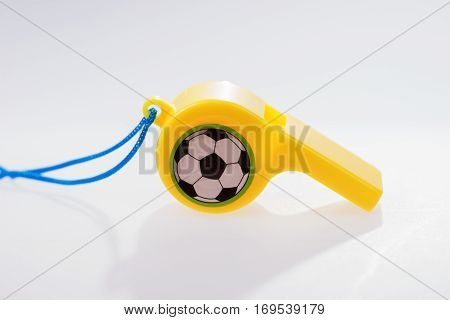 Colored plastic whistle with cord on white background