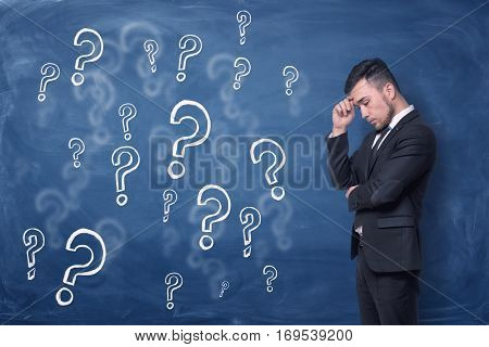 A businessman is standing thinking near blue blackboard background which is full of question marks. Puzzlement. Man thinking.