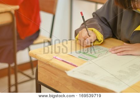 Students hand holding pencil writing doing examination background school students in exam classroom educational school