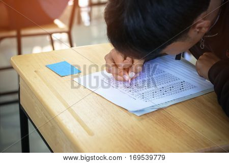 Thai students writing on a paper for exams test paper and admissions in high school with in Thailand