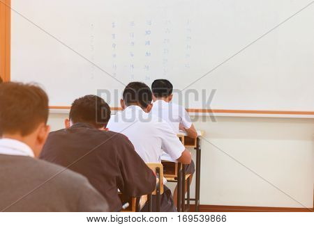 School students in uniform attending examination in a classroom in educational school: view of college people having exams in class on seat rows