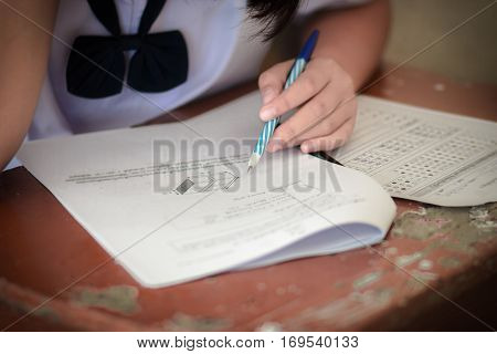 Thai students writing on a paper for exams test paper and admissions in high school with uniform in Thailand