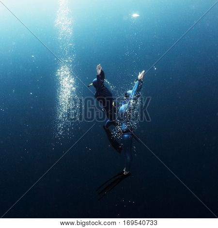 Two free divers ascending from the depth close to each other with lots of bubbles