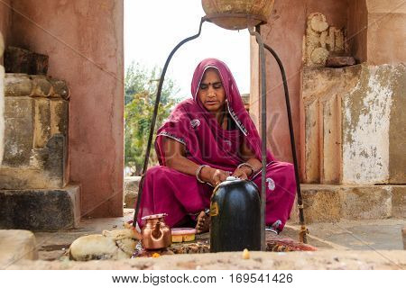 Abhaneri India 21st January 2017 -A Hindu woman worshipping a Shiva Lingam at the Harshat Mata Temple in Abhaneri Rajasthan India.