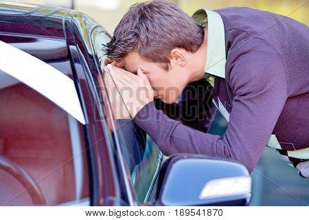Young man looking at new car