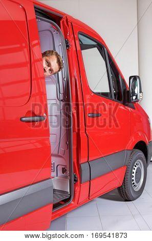 Young man peeking through van door