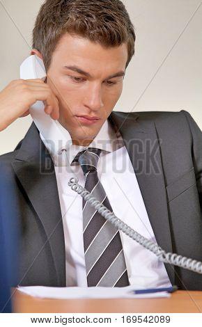 Businessman conversing on landline phone