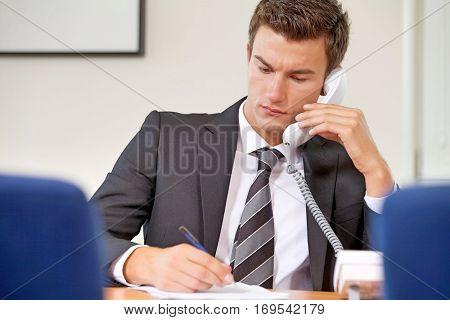 Businessman conversing on landline phone while writing on paper