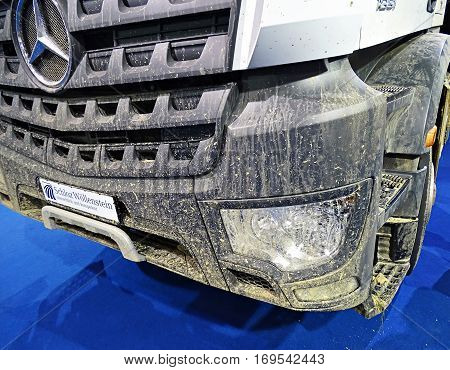 Chemnitz, Germany - October 4, 2015: Muddy front end of a truck of the type Mercedes-Benz Arocs 1851 with the typical Mercedes star. Mercedes-Benz is a trademark of vehicles of Daimler AG.