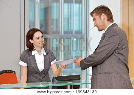 Young caucassian secretary assisting businessman
