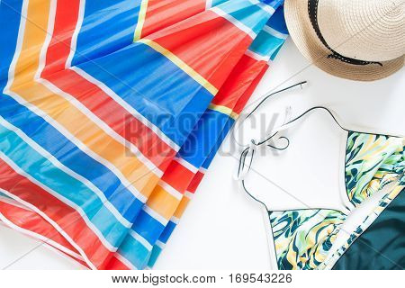 Overhead view of summer items with colorful umbrella swimwear and hat on white background