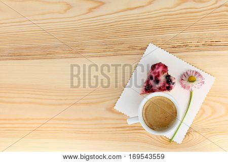 frothy coffee with berry Cake in the shape of a heart and a flower on a light wooden surface / morning surprise for beloved