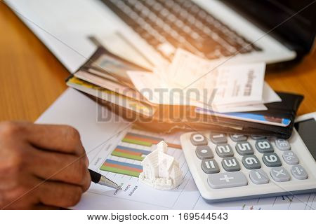Concept,Pen in hand and slip on pocket money with calculate income and expenses. to buy a house.
