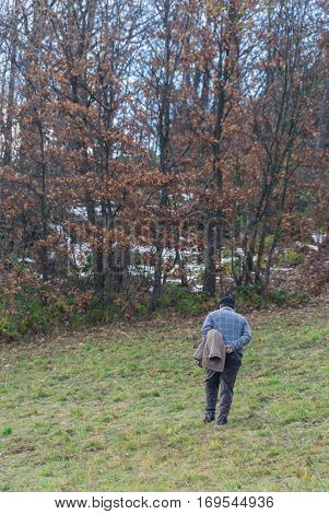 Old man walking up the hill towards the forest with hands on his back. Lifetime concept