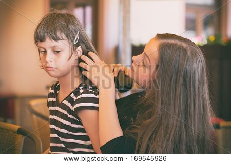 Two young girls while combing hair