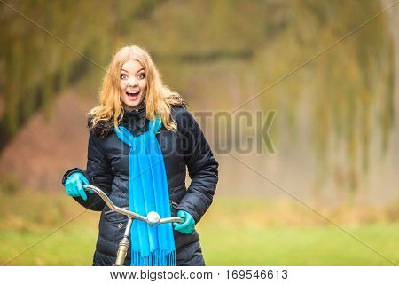 Happy active woman with bike bicycle in fall autumn park. Glad young girl in jacket and scarf relaxing. Healthy lifestyle and recreation leisure activity.