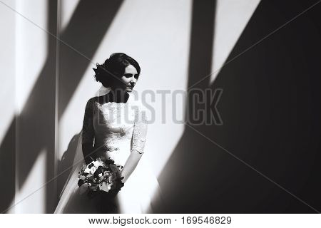 Balck and white portrait of beautiful luxury bride. geometric shadows on the wall
