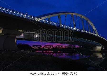 The majestic Main Street Bridge in Columbus, Ohio at sunset offers a glimpse of the railroad bridge in a distance.