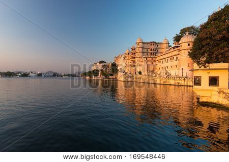 Udaipur Cityscape At Sunset. The Majestic City Palace On Lake Pichola, Travel Destination In Rajasth