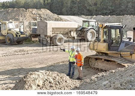 Supervisor showing something to colleague at construction site