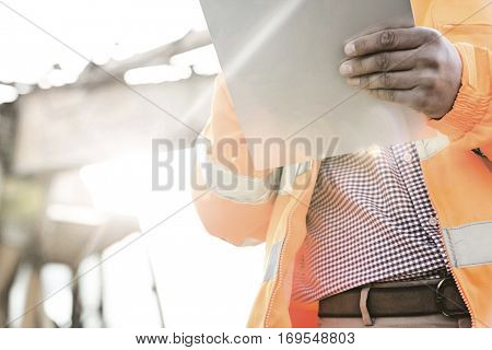 Midsection supervisor holding clipboard at construction site on sunny day