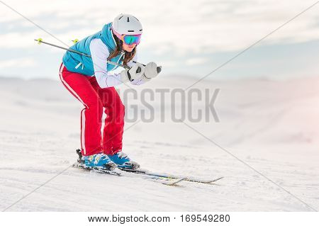 Girl woman skier in downhill position in ski resort