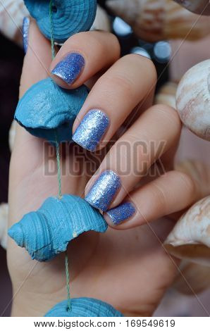 Female hands with blue glitter nail design holding sea shell.