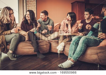 Group of multi ethnic young friends eating pizza in home interior