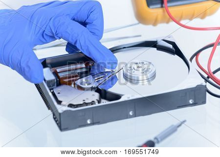 Service man fixing disk failure, hands protected with gloves.