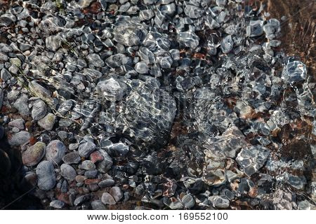 Photo gray smooth stones of different sizes, which are under the clear water stream with ripples on the surface
