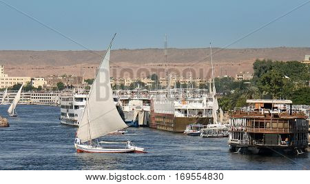 The River Nile with many boats and felluca's sailing along the river taking tourists on their trip along the Nile in Egypt