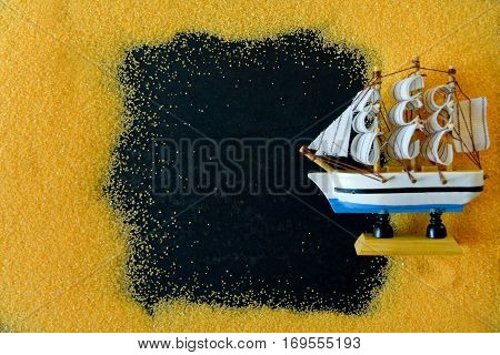 Bottle with ship inside lying on the beach. Conceptual image