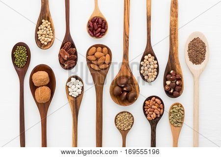 Different Kind Of Beans And Lentils In Wooden Spoon On White Wood Background. Mung Bean, Groundnut,