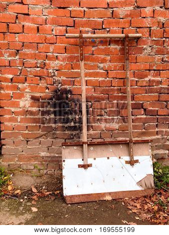 Shovel for snow cleaning is waiting for work near brick wall