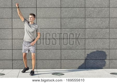 Full length of young jogger with clenched fist standing against tiled wall