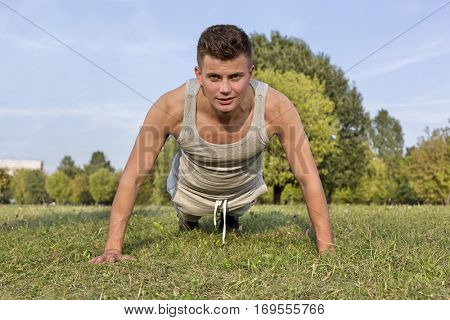 Portrait of young man doing pushups in park
