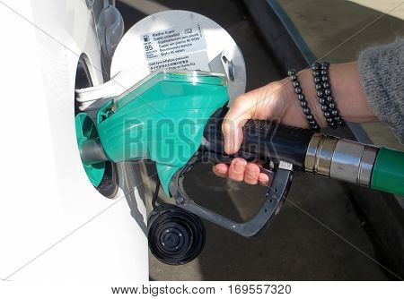 Woman filling car with petrol at filling station