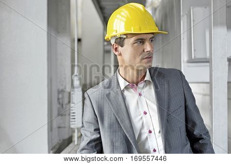 Young male supervisor wearing hard hat looking away in industry